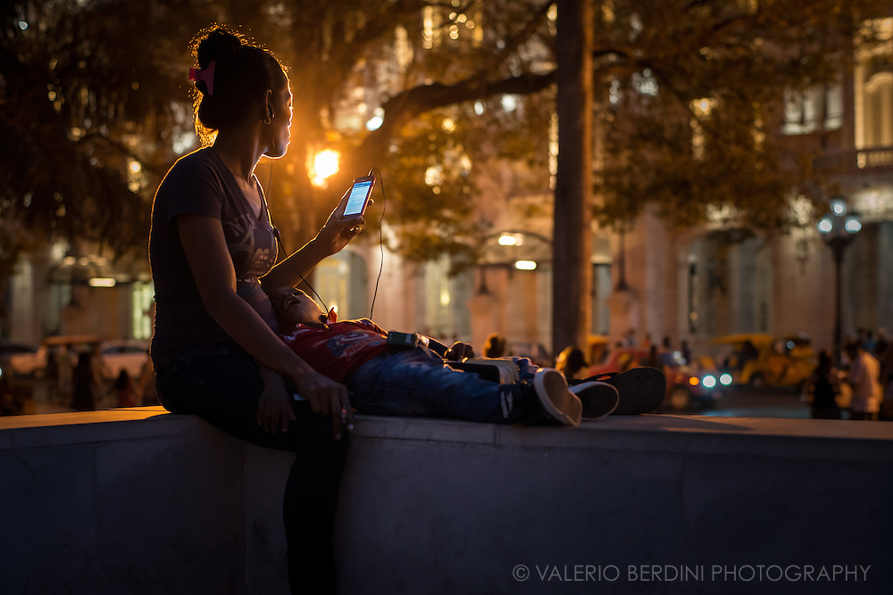 A mother with her child asleep, browse the internet in Parque Central in Havana, Cuba, on the afternoon of 28 December 2015. Her phone reads &quot;Pagina web no disponible&quot; (web page not accessible). Despite wi-fi is a great news for Cuba, the lines are not yet very reliable and the government does not allow every website and web service. This woman did not notice and was not aware of the photographer presence. This photo was not staged.<br />