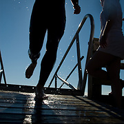 An athlete runs up a gangplank and onto the dock in waterfront park.  He is silhouetted by the sun.  Droplets of water fly everywhere.  2007 Shipbuilders Triathlon in Bath, Maine.