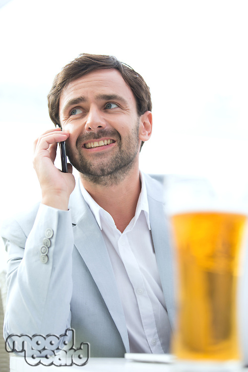Happy businessman looking away while using mobile phone at outdoor restaurant