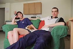 Two residents sitting on sofa in shared living space of homeless hostel with pet dog,