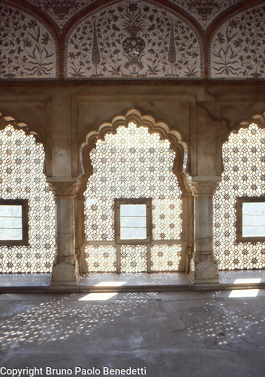 Carved windows in indo islamic style.Soft mood given by the sunlight filtering hough the carved windows in marble in room interior in the Amber palace.