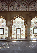 room interior in the Amber palace. Carved windows in indo islamic style.Soft mood given by the sunlight filtering hough the carved windows in marble.