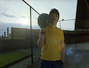 Young man holding basketball and looking straight at camera.