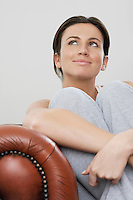 Young woman relaxing on sofa looking up