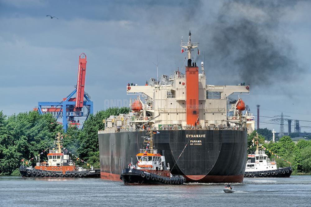 Drei Schlepper wenden ein Schiff im Hafenbecken vor der Rethe-Hebebrücke