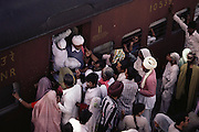 Pilgrims jamming the trains in Hardiwar station. Every 12 years, millions of devout Hindus celebrate the month-long festival of Kumbh Mela by bathing in the holy waters of the Ganges at Hardiwar, India. Hundreds of ashrams set up dusty, sprawling camps that stretch for miles. Under the watchful eye of police and lifeguards, the faithful throng to bathe in the river.