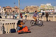 Lido di Ostia, Roma<br /> Il pontile, il punto più caratteristico ed il più suggestivo di Ostia, un musicista suona la chitarra.<br /> Lido di Ostia, Rome<br /> The wharf, the most characteristic and the most evocative of Ostia. A musician plays the guitar.