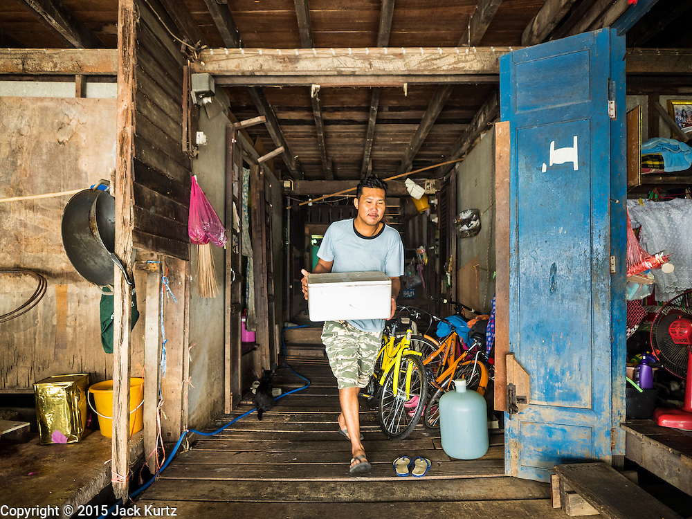 05 OCTOBER 2015 - BANGKOK, THAILAND: A man packs his belongings out of his home in the Wat Kalayanamit neighborhood. Fifty-four homes around Wat Kalayanamit, a historic Buddhist temple on the Chao Phraya River in the Thonburi section of Bangkok, are being razed and the residents evicted to make way for new development at the temple. The abbot of the temple said he was evicting the residents, who have lived on the temple grounds for generations, because their homes are unsafe and because he wants to improve the temple grounds. The evictions are a part of a Bangkok trend, especially along the Chao Phraya River and BTS light rail lines. Low income people are being evicted from their long time homes to make way for urban renewal.        PHOTO BY JACK KURTZ