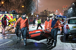 © Licensed to London News Pictures . 26/12/2015 . Salford , UK . Mountain rescue team carrying a dingy along Lower Broughton Road as residents were evacuated from surrounding streets following flooding . Photo credit : Joel Goodman/LNP