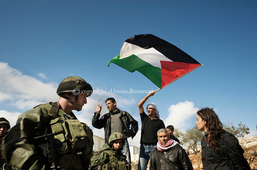 A Palestinian waves his national flag above  Israeli soldiers during a protest against Israel's controversial separation barrier in the West Bank village of Maasarah, near Bethlehem, on November 13, 2009..© ALESSIO ROMENZI.