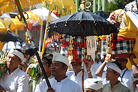 A temple procession with people bearing processional umbrellas, offerings and religious figures in Bali, Indonesia.