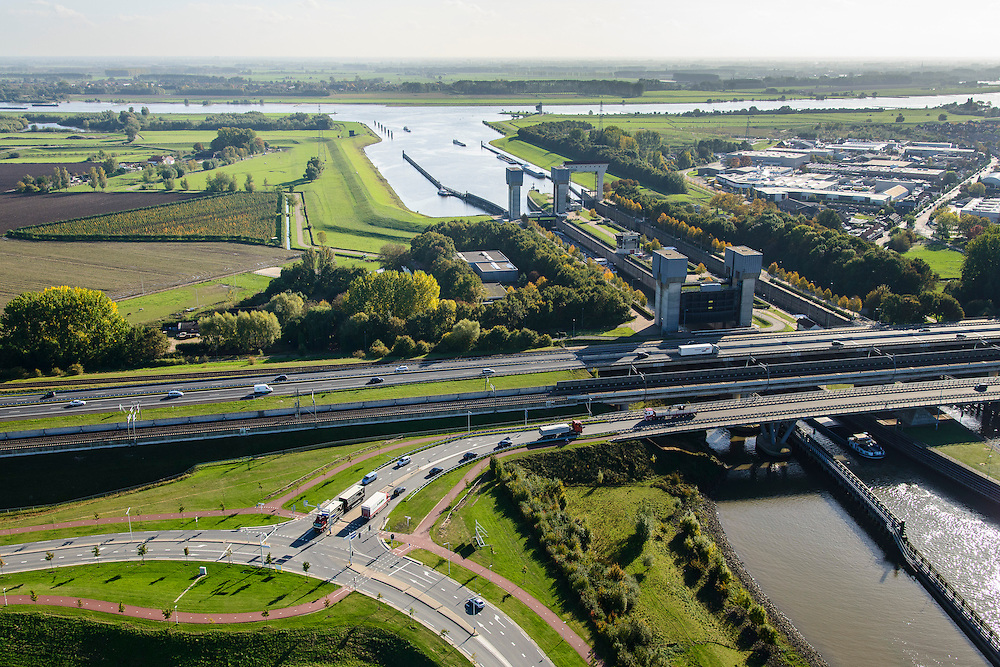 Nederland, Gelderland, Tiel, 24-10-2013; Betuweroute en autosnelweg A15 kruisen het Amsterdam-Rijnkanaal ter hoogte van de Prins Bernhardsluis, rivier de Waal in de achtergrond. Goederentrein nadert de brug over het kanaal. Binnenvaartschepen in de sluiskolk. Rechtsboven bedrijventerrein Tiel.<br /> Betuweroute, railway from Rotterdam to Germany,  and A15 motorway cross the Amsterdam-Rhine Canal at the Prince Bernhard lock, the Waal river in the background. Barges in the lock chamber.<br /> luchtfoto (toeslag op standaard tarieven);<br /> aerial photo (additional fee required);<br /> copyright foto/photo Siebe Swart.