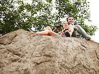 Couple sitting on rock woman holding binoculars. low angle view
