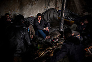 Migrants from Afghanistan are seen warming up in one of the abandoned wearhouses in Belgrade train station. Belgrade, Serbia. March 19th, 2017. Federico Scoppa/CAPTA