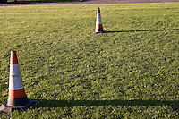 Parking cones used as football goal posts in a suburban park field