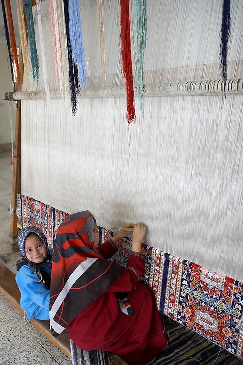Children weaving carpets in carpet factory near Cairo, Egypt