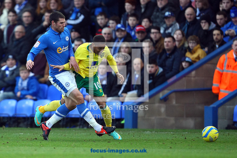 Picture by Paul Chesterton/Focus Images Ltd +44 7904 640267.05/01/2013.Simeon Jackson of Norwich is fouled by Michael Bostwick of Peterborough during the The FA Cup match at London Road, Peterborough.