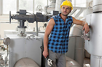 Young labor holding wrench while leaning on industrial machine