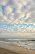 Waves roll in to the beach from the Atlantic Ocean as the seasons change on an early September morning just before the summer ends and it turns to autumn. The dramatic blue sky is filled with altocumulus clouds and stratus clouds, Palm Coast, Florida, USA, September 2011.