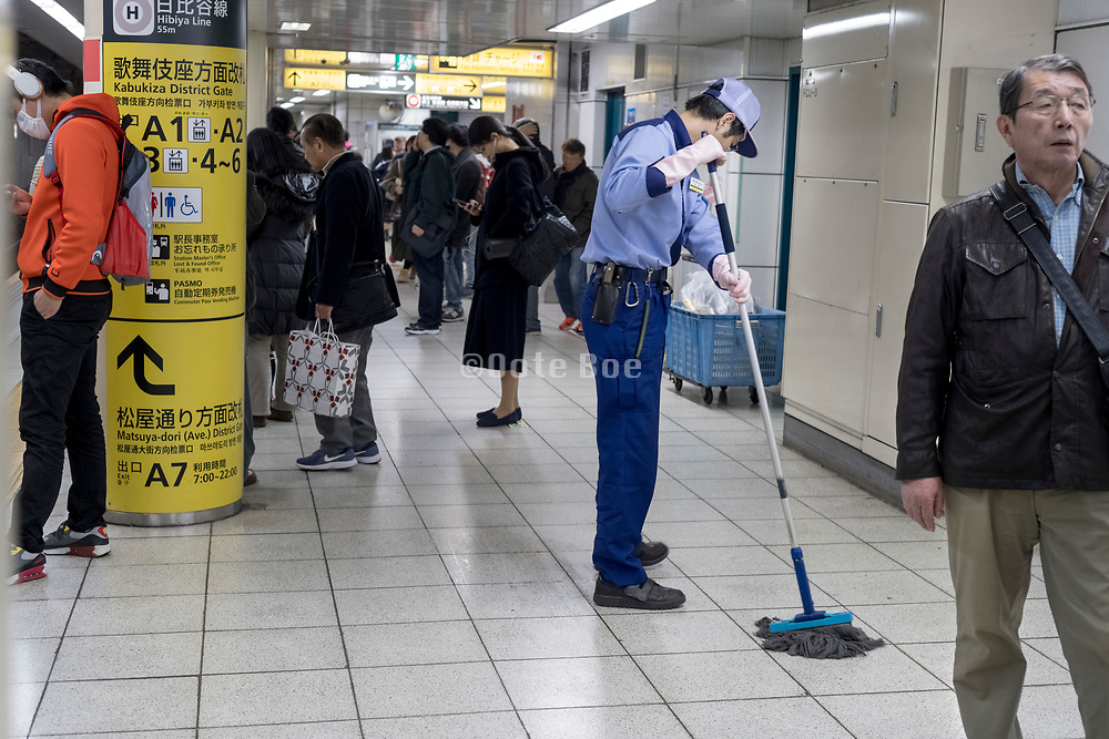 station staff worker cleaning the platform floor Japan Tokyo