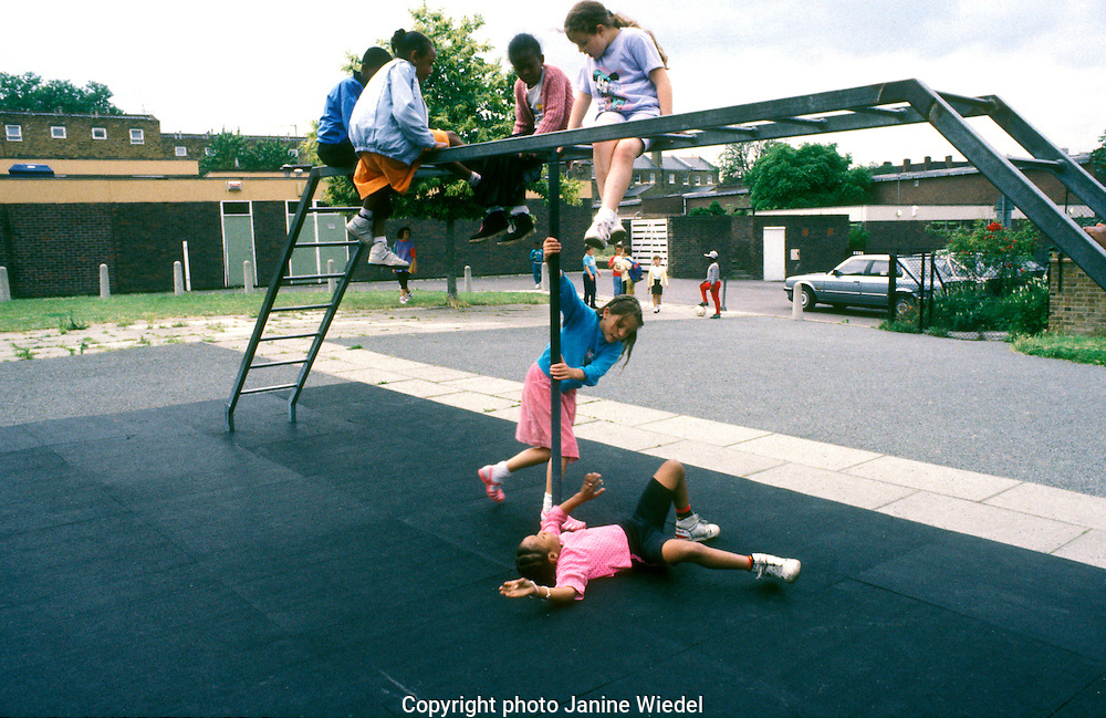 Young children playing on climbing frame in playground with rubber tiles for safety.
