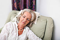 Senior woman sleeping on armchair at home