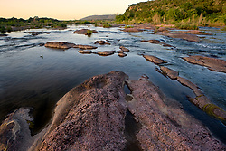 Stock photo of pink granite rocks sticking out of the Llano River in the Texas Hill Country at sunset