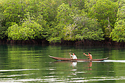 Mentawai villagers paddle past in a dug out canoe, Mentawai Islands, Indonesia