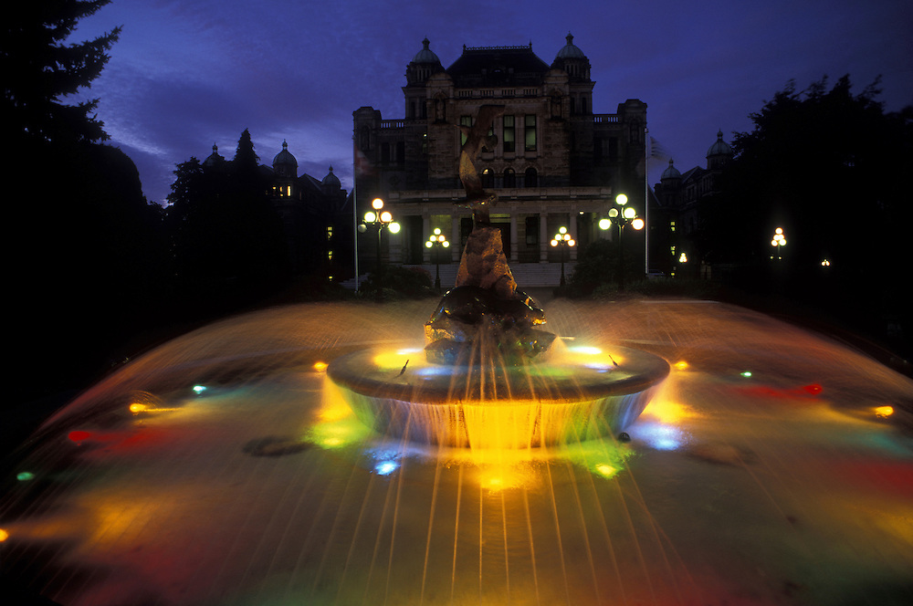 Canada, British Columbia, Victoria, Colored fountain behind Provincial Parliament building at twilight