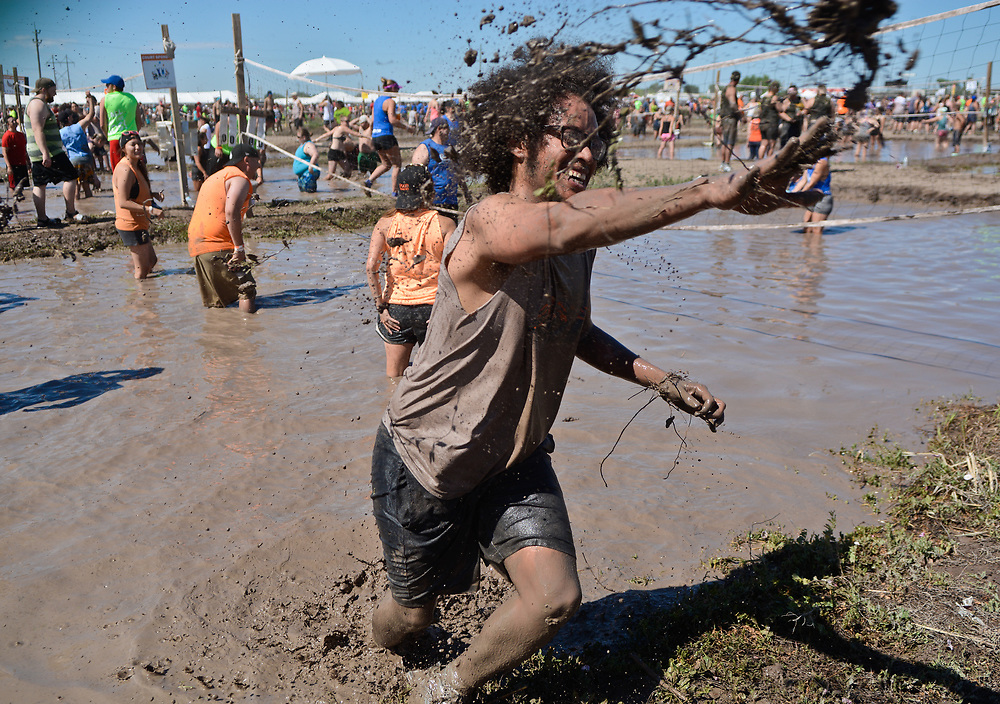 mkb060317e/metro/Marla Brose --  Roger Moore, Jr., throws a handful of mud as he emerges from a mudd volleyball court during the Carrie Tingley Hospital Foundation's 23rd annual Mudd Volleyball tournament, Saturday, June 3, 2017. (Marla Brose/Albuquerque Journal)
