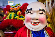 "09 FEBRUARY 2013 - BANGKOK, THAILAND:  A ""Laughing Buddha"" accompanies a parade of Lion Dancers on Chinese New Year in Bangkok. The Buddhas are comic and acrobatic characters who interact with the crowd and tease the lion with a fan or a ball. The lion in turn will play with, chase, or even bite and kick the buddha depending on its mood. Because it is difficult for the lion dancers to see, the Buddhas also help the lions find their ""food"", etc. Bangkok has a large Chinese emigrant population, most of whom settled in Thailand in the 18th and 19th centuries. Chinese, or Lunar, New Year is celebrated with fireworks and parades in Chinese communities throughout Thailand. The coming year will be the ""Year of the Snake"" in the Chinese zodiac.   PHOTO BY JACK KURTZ"