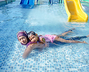 A portrait of Ibu Ratna and Amel at a water park.  They love to swim and play on the waterslide. <br />
