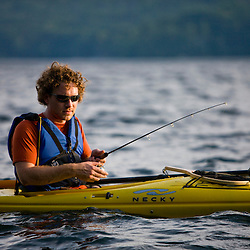 A man fishing from his kayak on Lake Sunapee at Mount Sunapee State Park in Newbury, New Hampshire.