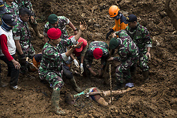 February 6, 2018 - Bogor, Indonesia - Rescue workers uncover a victim. Five people were buried alive from landslide at Maseng-Cijeruk-Bogor-West Java. The landslide happen because heavy rain hit the area and poor construction of the rail way near the houses built below the rail way, causing three houses where 9 people live there, 5 were killed from the landslide. Police and Millitary continue search and rescue along with evacuations. (Credit Image: © Donal Husni via ZUMA Wire)