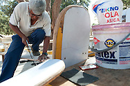 Juan Lengua Salvador works on the creation of a sandboard at the oasis village of Huacachina in Peru.  Each board takes about a full day to complete.