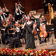 """November 11, 2012 - New York, NY : Accompanied by members of the Metropolitan Opera Orchestra and The New York Choral Society, and conducted by Patrick Summers (standing at right), soprano Liudmyla Monastyrska (standing at center) performs Giuseppe Verdi's """"Vieni, t'affretta"""" from Macbeth during the 2012 Richard Tucker Gala and concert in Lincoln Center's Avery Fisher Hall on Sunday evening. CREDIT: Karsten Moran for The New York Times"""