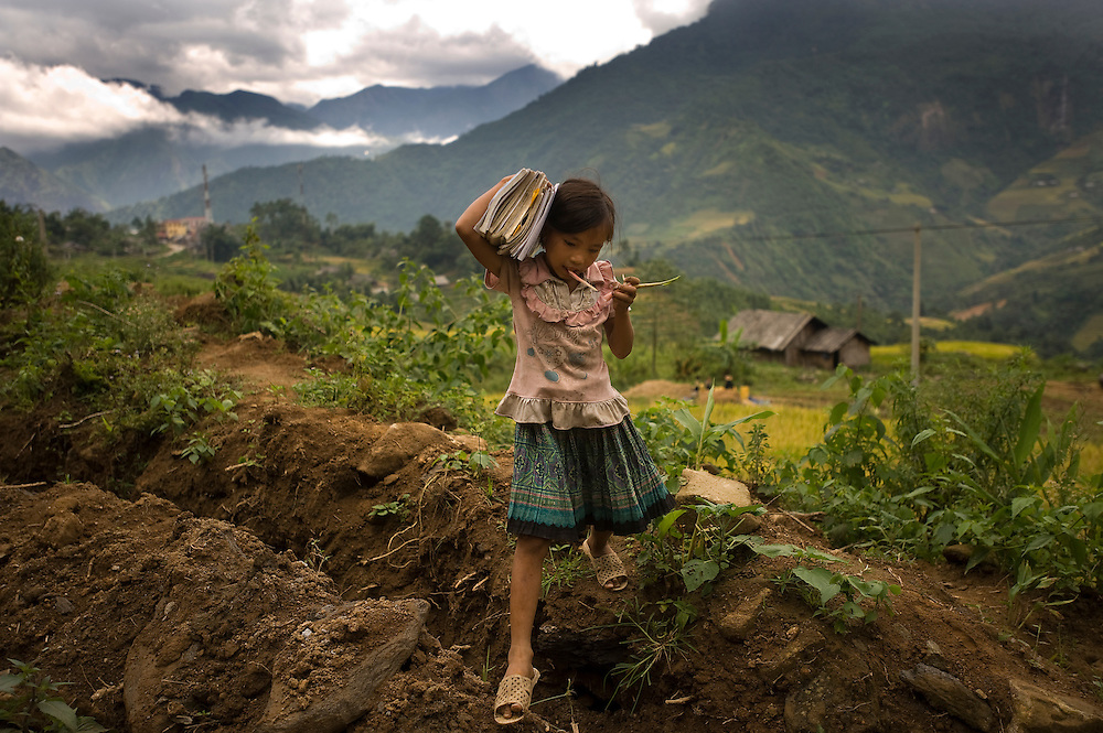A little girl make her way home from school, as she hops over a irrigation canal in Sa Pa, Vietnam.