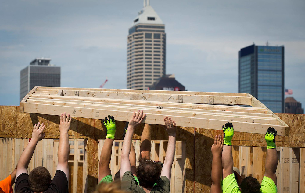 Volunteers from Angie's List band together to lift a framed section as they build a house for Habitat for Humanity in Indianapolis.