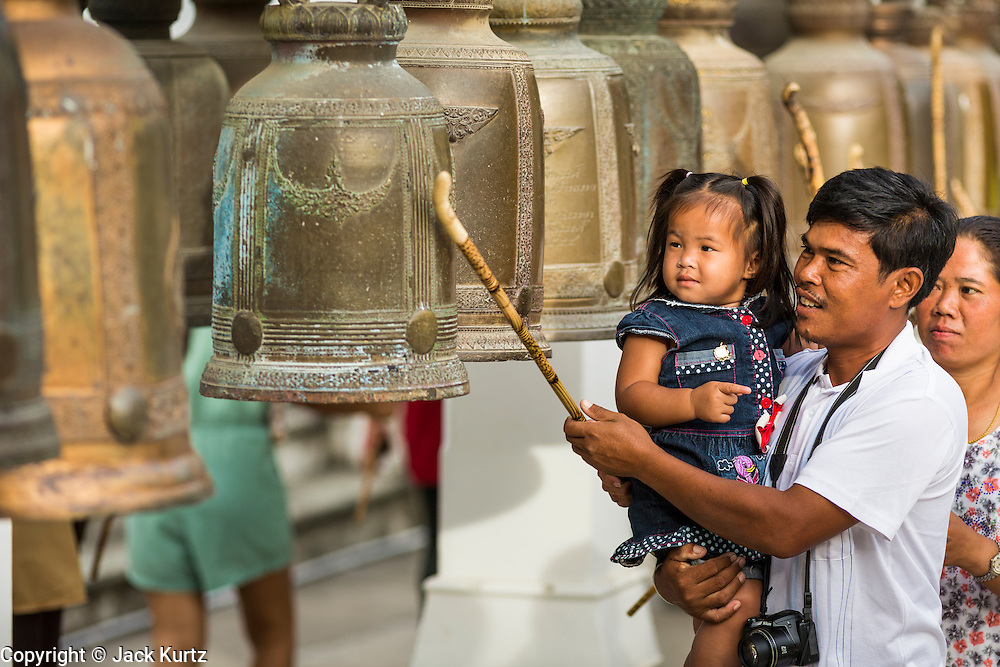 "22 JULY 2013 - PHRA PHUTTHABAT, THAILAND:  People ring prayer bells during the Tak Bat Dok Mai at Wat Phra Phutthabat in Saraburi province of Thailand, Monday, July 22. Wat Phra Phutthabat is famous for the way it marks the beginning of Vassa, the three-month annual retreat observed by Theravada monks and nuns. The temple is highly revered in Thailand because it houses a footstep of the Buddha. On the first day of Vassa (or Buddhist Lent) people come to the temple to ""make merit"" and present the monks there with dancing lady ginger flowers, which only bloom in the weeks leading up Vassa. They also present monks with candles and wash their feet. During Vassa, monks and nuns remain inside monasteries and temple grounds, devoting their time to intensive meditation and study. Laypeople support the monastic sangha by bringing food, candles and other offerings to temples. Laypeople also often observe Vassa by giving up something, such as smoking or eating meat. For this reason, westerners sometimes call Vassa the ""Buddhist Lent.""    PHOTO BY JACK KURTZ"