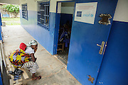 A woman waits with her child at the Libreville health center in Man, Cote d'Ivoire on Wednesday July 24, 2013.