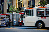 Muni customers wait in line at a bus stop along Market St during the morning commute | June 27, 2012