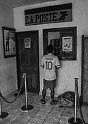 Camopi, Guyane, 2015.<br /> <br /> Jour du versement des allocations &agrave; la Poste de Camopi. Les perspectives professionnelles de la commune sont rares. Seule une cinquantaine d&rsquo;emplois sont r&eacute;partis entre la gendarmerie et la l&eacute;gion qui utilisent une dizaine de piroguiers, la poste qui occupe un salari&eacute;, le nouveau Parc National de Guyane, l&rsquo;&eacute;cole, la municipalit&eacute; et le d&eacute;partement. A Camopi, pratiquement la totalit&eacute; de la population active per&ccedil;oit le RSA et les allocations familiales. <br /> <br /> La continuit&eacute; du service bancaire se r&eacute;sume &agrave; la seule pr&eacute;sence d&rsquo;un bureau de Poste dont les caisses sont souvent vides en dehors des p&eacute;riodes de versement des prestations sociales. L&rsquo;argent arrive alors par h&eacute;licopt&egrave;re et peu avant le 7 de chaque mois, au moment des allocations, des familles enti&egrave;res se d&eacute;placent sur le fleuve depuis les villages de Trois-Sauts ou les &eacute;carts de la rivi&egrave;re Camopi pour venir toucher leurs subsides de l&rsquo;&Eacute;tat.<br /> <br /> Consid&eacute;r&eacute;e comme la commune la plus enclav&eacute;e de Guyane, &agrave; Camopi les activit&eacute;s &eacute;conomiques sont quasi inexistantes. Il n&rsquo;y a pas de commerce en dehors du restaurant r&eacute;serv&eacute; exclusivement &agrave; l&rsquo;h&eacute;bergement et aux repas des escadrons de Gendarmes mobiles qui se relaient sur place. L&rsquo;argent est donc imm&eacute;diatement d&eacute;pens&eacute; &agrave; Vila Brasil, un village br&eacute;silien &agrave; l&rsquo;origine clandestin, devenu district d&rsquo;Oiapoque en 2011 et qui fait face au bourg. Construit dans un premier temps pour alimenter les sites d&rsquo;orpaillages ill&eacute;gaux, ce comptoir vit maintenant de l&rsquo;argent d&eacute;pens&eacute; par les Am&eacute;rindiens de la commune. Les habitants du bourg viennent s&rsquo;y approvisionner, acheter du poisso