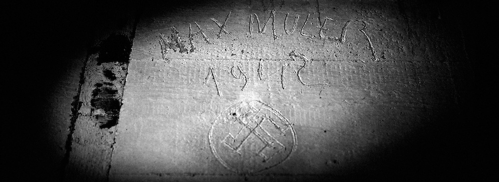 "POINTE-DU-HOC, FRANCE - MARCH 14: The name of a suspected German soldier ""Max Muler, 1942"" and a Nazi Swastika are seen carved into the wall of a German personnel bunker, 14 March, 2009, Pointe-du-Hoc, France. Situated 6km west of Omaha Beach on a clifftop housing a battery of 155mm guns and the ability to fire on both Utah and Omaha, Pointe-du-Hoc was a formidable German defense to be silenced on D-Day by 225 soldiers from the US 2nd Ranger Battalion. The frontal assault required the Rangers to scale the 100ft cliff face under direct fire from the Germans above. After taking the battery with limited resistance the Rangers quickly realized the 155mm guns had not been installed and were inactive in a nearby field. More than half the Rangers, however, were killed or wounded as they fended off attacks for the next 48 hours. D-Day is regarded amongst historians as possibly the most defining day of the 20th Century, when allied forces comprising of 175,000 fighting men transported by 5,333 ships and 11,000 aircraft, landed in Nazi-occupied France and went on to liberate Europe. (Photo by Warrick Page)"
