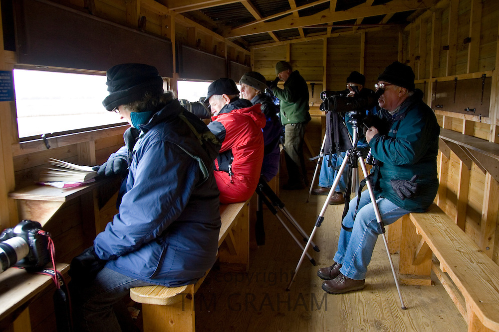 Birdwatchers inside bird hide watch migrating geese over-wintering near Holkham, Norfolk, East Anglia, United Kingdom