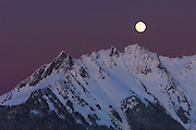 The full moon rises over Nooksack Ridge in Washington's North Cascades just after sunset. The mountain is lit by alpenglow, a natural lighting phenomenon that causes mountains to glow white shortly after sunset and before sunrise.