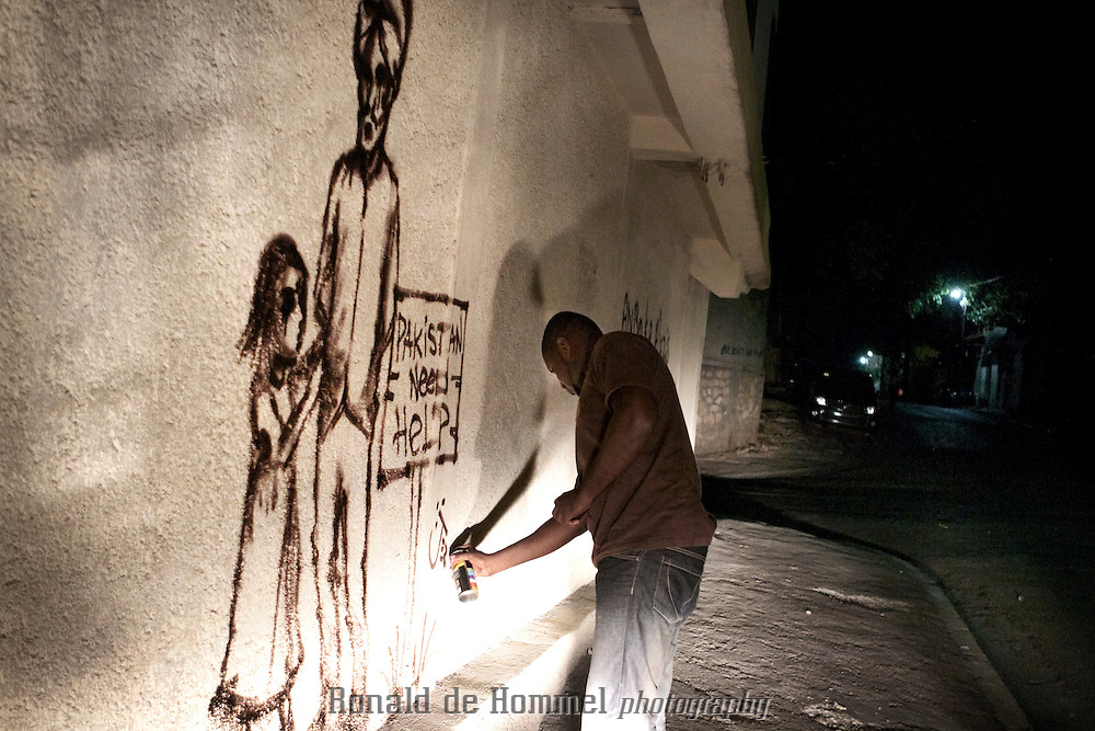 In Port au Prince graffiti artist Jerry Moise Rosembert reviews his most recent work. He just finished a new piece in support of the victims of the Pakistan flood victims in the fall of 2010.