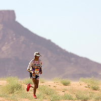 28 March 2007: Nine times winner of the men race Lahcen Ahansal of Morocco runs through dunes before check point 4 during fourth and longest stage of the 22nd Marathon des Sables between jebel Zireg and west of Kfiroun (43.8 miles). The Marathon des Sables is a 6 days and 151 miles endurance race with food self sufficiency across the Sahara Desert in Morocco. Each participant must carry his, or her, own backpack containing food, sleeping gear and other material.