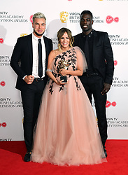 Caroline Flack with the reality and constructed factual award on behalf of Love Island with participants Chris Hughes and Marcel Somerville in the press room at the Virgin TV British Academy Television Awards 2018 held at the Royal Festival Hall, Southbank Centre, London.