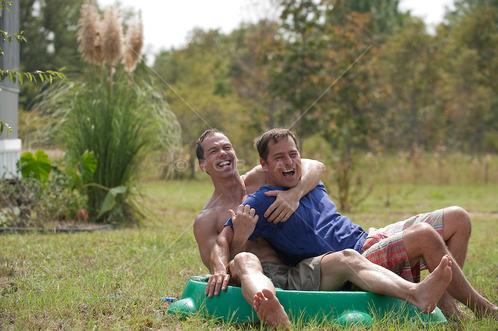Two men being playful while in a kiddie pool