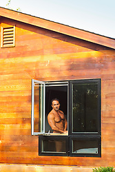 nude man looking out a window in a modern house